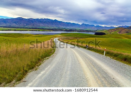 The road crosses the hills of South Island. Christchurch Road. The landscape of New Zealand. The hills were overgrown with yellowed grass. The concept of active, environmental and photo tourism #1680912544