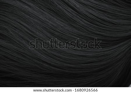 Brunette or brown hair. Female long dark hair in black. Beautifully laid curls. Closeup texture in a dark key. Hairdressing, hair care and coloring. Shading gray hair. Background with copy space. #1680926566