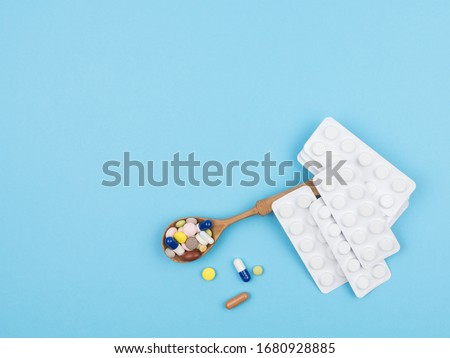 Spoon with medications and blisters of pills on a blue background. The view from the top. #1680928885