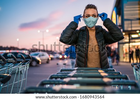 A woman wears medical protective gloves and a mask while shopping groceries. #1680943564