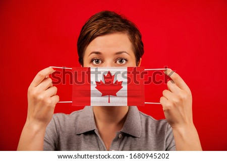 Coronavirus COVID-19 in Canada. Woman in medical protective mask with the image of the flag of Canada. #1680945202