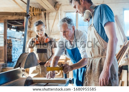 Experienced master carpenter transferring knowledge to his younger colleagues