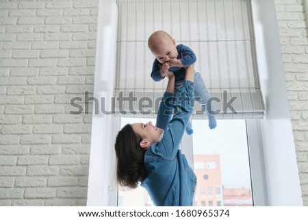 Happy young beautiful mother playing with toddler son, woman raising baby up, flying and laughing boy. Family is happy at home, near window, copy space #1680965374