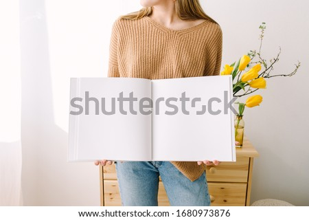 White book mockup. Opened square empty book. Album with clean pages in hands of woman. Clean book mockup. Woman is standing in forward of chest of drawers with a book. Mock-up is ready to design #1680973876