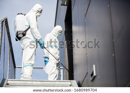 Staff in clean suits disinfecting public places #1680989704