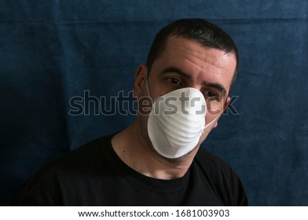 Portrait of a sick man with a face mask suffering from coronavirus disease. The face shows surprise. Pandemic caused by a virus Covid-19, concept. #1681003903
