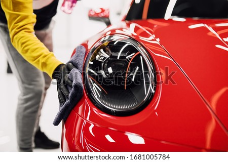 A man cleaning car with cloth, car detailing (or valeting) concept. Selective focus.  Royalty-Free Stock Photo #1681005784
