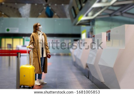 Woman with luggage stands at almost empty check-in counters at the airport terminal due to coronavirus pandemic/Covid-19 outbreak travel restrictions. Flight cancellation.Quarantine all over the world #1681005853