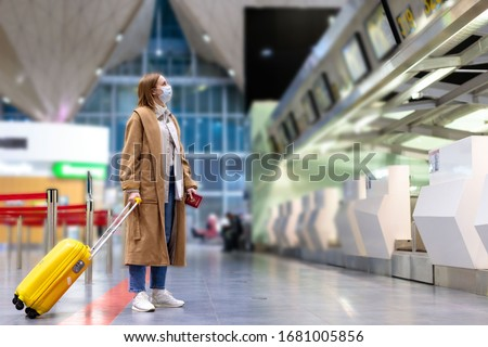 Woman with luggage stands at almost empty check-in counters at the airport terminal due to coronavirus pandemic/Covid-19 outbreak travel restrictions. Flight cancellation.Quarantine all over the world #1681005856