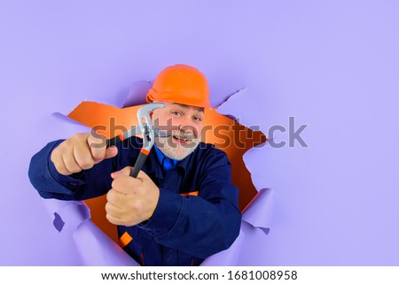Worker or builder in helmet with pliers looking through paper. Professional plumber holds pliers. Auto mechanic holds combination pliers. Builder with adjustable pliers. Bearded worker ready to work. #1681008958