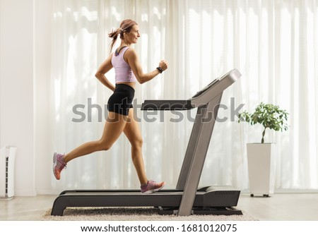 Full length profile shot of a fit woman running on a treadmill at home #1681012075