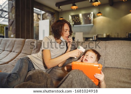 Family stay at home. Mother with little son. Coronavirus theme. Mom measures baby's temperature. #1681024918