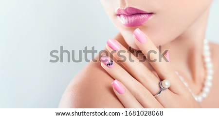 Nail art and design. Beautiful woman wearing make-up and pearl jewellery showing pink manicure with gems. Beauty fashion model. Skin care. Banner #1681028068
