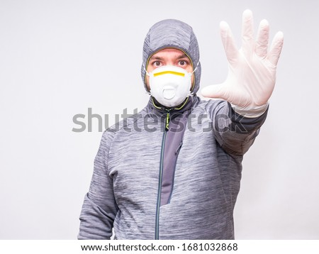 Man with hood and mask has an arm extended towards the camera with gloves as part of the individual protection equipment #1681032868