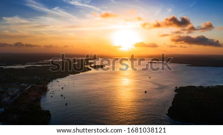 Beautiful coastline in Tibau do Sul during a bright summer sunset with a large river and boats in the background #1681038121