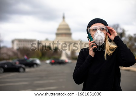 An American woman wears a mask and goggles at the U.S. Capitol building in Washington, D.C. to protect herself from the COVID-19 coronavirus. Royalty-Free Stock Photo #1681051030