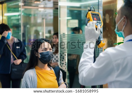 Asian people waiting for body temperature check before access to building for against epidemic flu covid19 or corona virus from wuhan in office by thermoscan or infrared thermal camera #1681058995