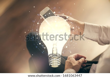 Double exposure of man's hands holding and using a digital device and bulb hologram drawing. Idea concept. #1681063447