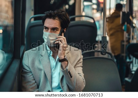 Depressing scene of a young man wearing a surgical mask during the coronavirus outbreak in Europe, talking on his mobile phone. Public transportation curfew. Royalty-Free Stock Photo #1681070713