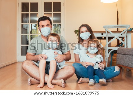 Beautiful young family wearing face masks against coronavirus world pandemic and staying home #1681099975