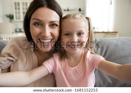 Smiling young mother and small preschooler daughter look at camera making selfie at home together, happy funny mom and little girl child have fun laugh take photo posing for self-portrait picture