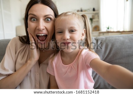 Funny millennial mom or nanny have fun posing for self-portrait picture with cute little girl, overjoyed happy young mother enjoy playful weekend with small daughter, make selfie on phone together