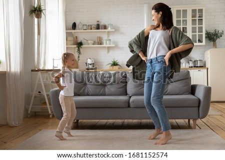 Happy young mom and little daughter dancing together having fun in modern living room, smiling active mother and small preschooler daughter feel overjoyed enjoy leisure family weekend at home #1681152574