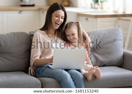 Overjoyed young mother and cute little daughter have fun relax at home together watch funny video cartoon on laptop, smiling mom and small girl child spend leisure time using computer playing game