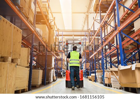 Storehouse employee in uniform working on forklift in modern automatic warehouse.Boxes are on the shelves of the warehouse. Warehousing, machinery concept. Logistics in stock. Royalty-Free Stock Photo #1681156105