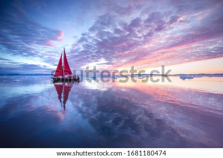 Sail boat with red sails cruising among ice bergs during sunrise. Disko Bay, Greenland. Royalty-Free Stock Photo #1681180474