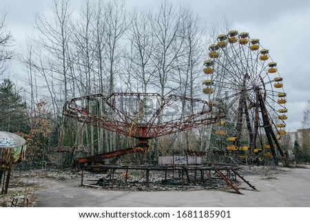 Prupyat, Chernobyl, Ukraine - April 30, 2019: Abandoned carousel and abandoned ferris at an amusement park in the center of the city of Pripyat, the Chernobyl disaster, the exclusion zone, a ghost tow #1681185901