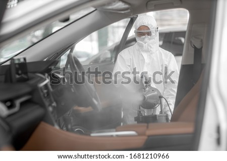 Disinfectant worker character in protective mask and suit sprays bacterial or virus in a car.