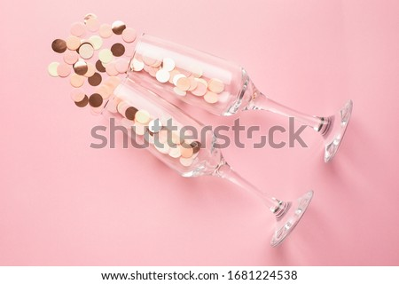 Champagne glasses with pink and gold confetti on pink color paper background minimal style #1681224538