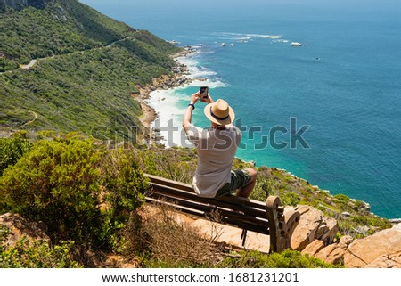 Traveler millennial guy taking panoramic photo by his phone in Cape of Good Hope, South Africa. Man in summer clothes enjoying breathtaking view. Summer holiday vacation relax time at seaside.