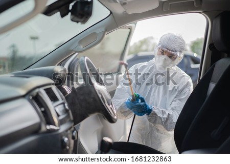 Virologist scientists wearing PPE kits are cleaning the virus in cars. Royalty-Free Stock Photo #1681232863