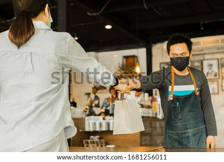 Social distance conceptual waiter giving food client at small business food. #1681256011