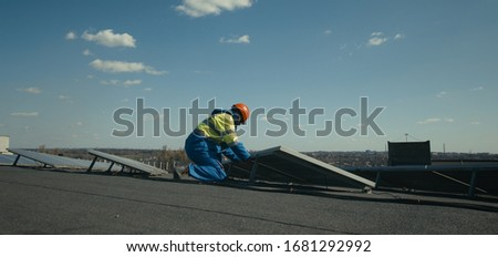 Medium shot of technician installing solar panel and then looking at camera #1681292992