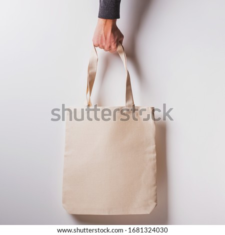 Man's hand holds blank cotton eco tote bag over the white wall, design mockup. #1681324030