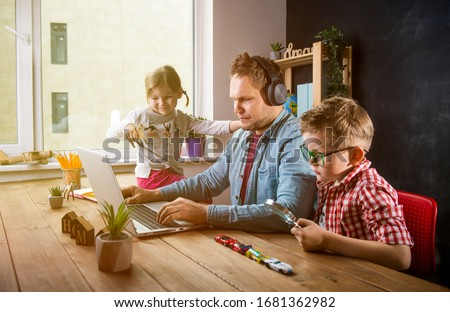 Work from home. School home education during quarantine. Father works with children boy and girl on table. #1681362982