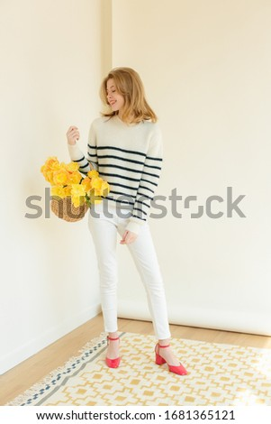 Shoot fashion campaign story. Charming model staying, wearing white textile sweater with stripes and creamy pants. Girl holding bunch of tulips flowers. Colorful carpet on floor. White Background.  #1681365121