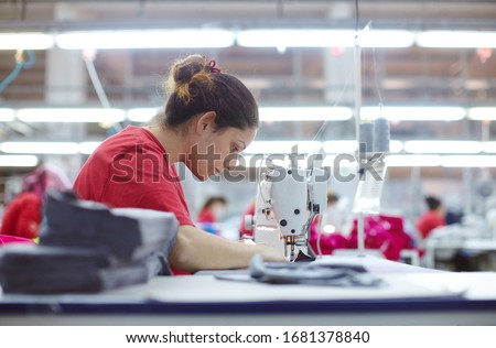 Young tailor seamstress working on textile factory Royalty-Free Stock Photo #1681378840