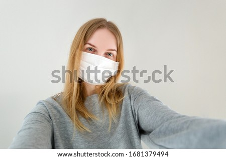 Woman with mask to protect from virus. The concept of the epidemic of the coronavirus. Stop the virus and Corona virus pandemic. Close up portrait of a pretty woman taking selfie #1681379494