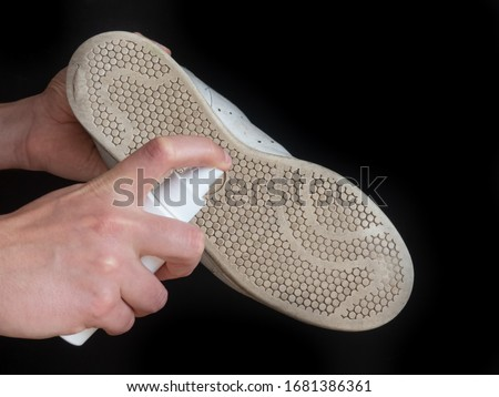 Hands sanitizes shoe sole against coronavirus. Disinfectant spray on the sole of shoe isolated on black background #1681386361