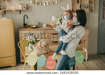Happy mother with daughter in her arms making selfie on kitchen background and easter eggs and tulips home on quarantine with medical mask. Coronavirus, illness, infection, flue, surgical bandage. Royalty-Free Stock Photo #1681428109