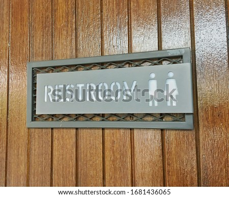 Modern metal sign of toilet in minimalism style is public restroom sign stick on wooden board background ,which has simple woman (female sex) ,man (male sex) picture icons as well-known symbol