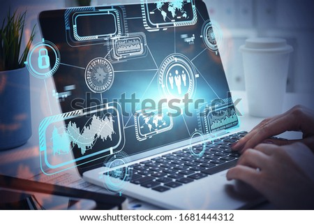 Hands of businesswoman typing on laptop in blurry office with double exposure of futuristic business interface. Concept of hi tech and programming. Toned image #1681444312