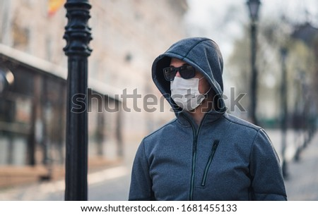portrait of a brunette man in a surgical dressing and black glasses against the backdrop of a modern building, coronavirus, disease, infection, quarantine, medical mask #1681455133