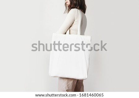 Urban mockup of tote bag. Girl holding white cotton tote bag on a white wall background. Template can be used for you design  #1681460065