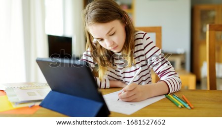 Preteen schoolgirl doing her homework with digital tablet at home. Child using gadgets to study. Education and distance learning for kids. Homeschooling during quarantine. Stay at home entertainment. #1681527652