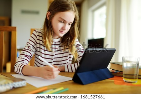 Preteen schoolgirl doing her homework with digital tablet at home. Child using gadgets to study. Education and distance learning for kids. Homeschooling during quarantine. Stay at home entertainment. #1681527661